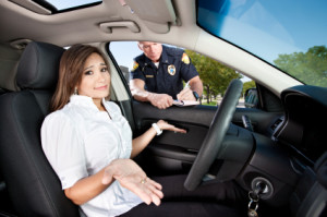 A beautiful young woman sitting in the drivers seat of her car, holds up her hands and shrugs with hopelessness as a police officer stands outside her vehicle writing her a moving violation ticket.