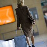 Businesswoman walking with luggage in airport baggage claim area, rear view (tilt)